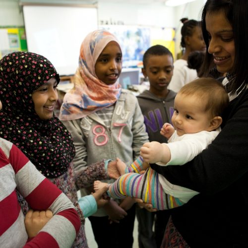 mother and baby visiting a classroom of students