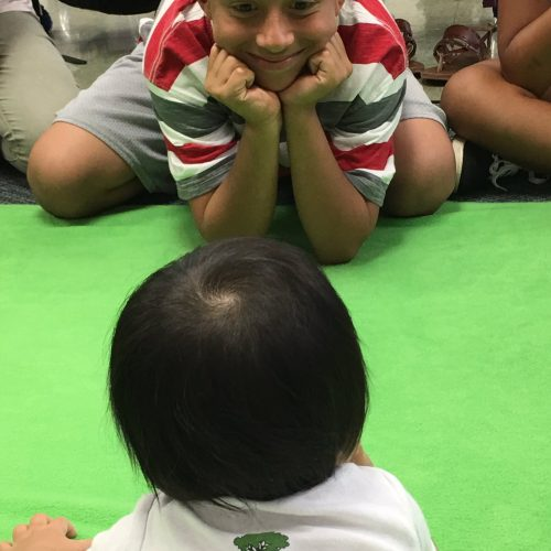 a baby and a student look at each other