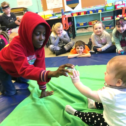 a student plays with a baby